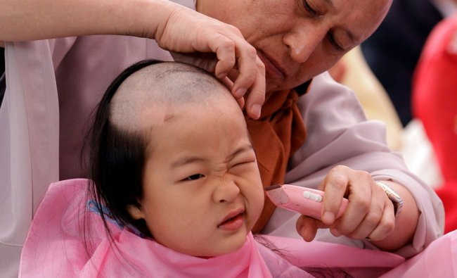 A South Korean Buddhist monk shaves the head of Hye Oh during a service