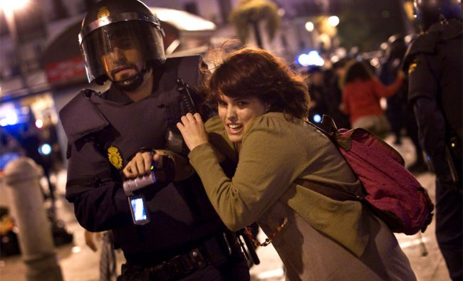 A woman protester is led away by a police officer at Puerta del Sol square in Madrid, Spain