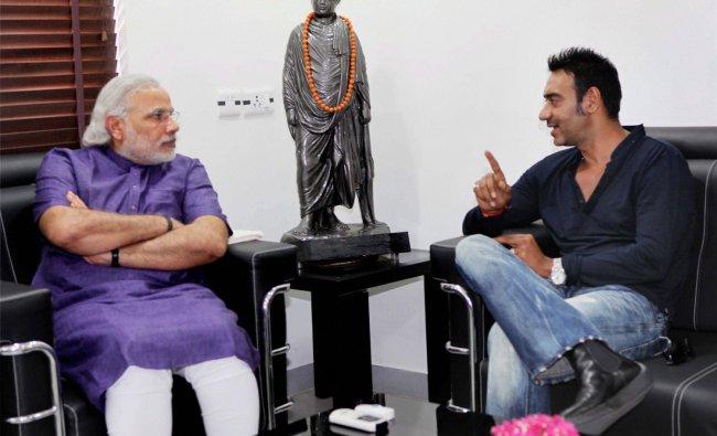 Gujarat Chief Minister Narendra Modi intreacts with film actor Ajay Devgn