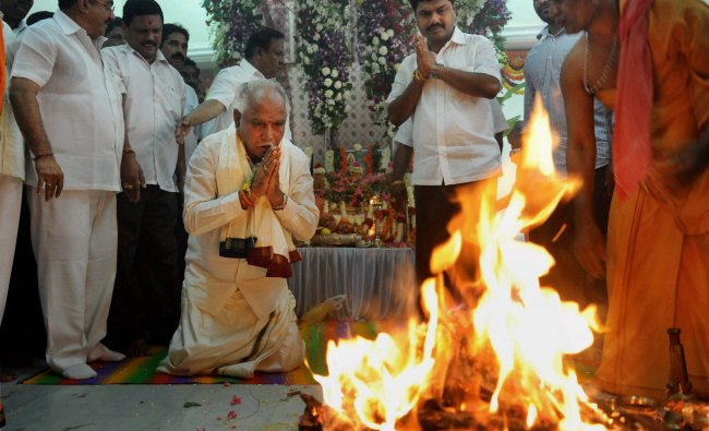 B S Yeddyurappa with his son MP B Y Raghvendra performs prayers at his new office...
