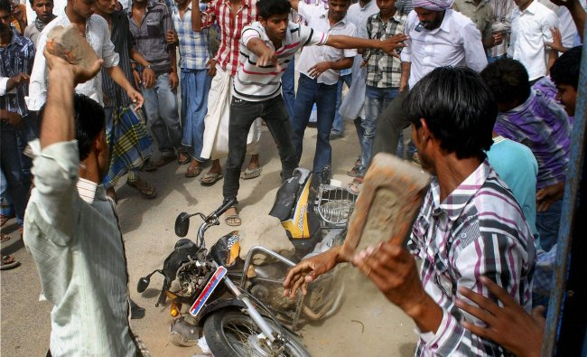 Angry mob damaging a police motorcycle during a protest...