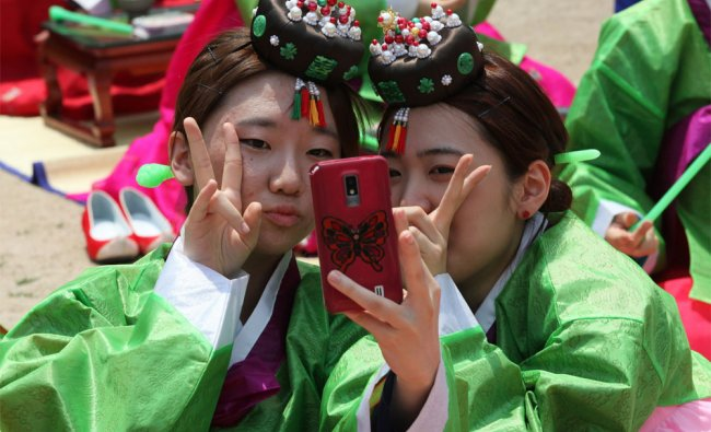 SKorean girls in traditional dresses take a picture of themselves after 40th Coming of Age Ceremony