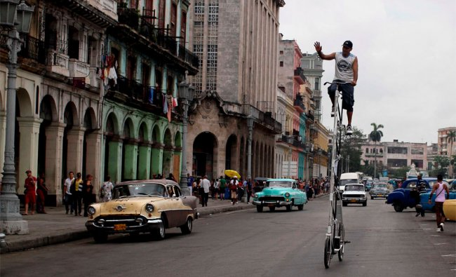 Felix Girola waves to people as he takes his self-made bicycle for a spin through downtown Havana