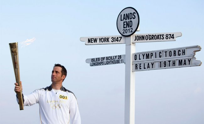 Ben Ainslie holds the Olympic torch at the start of London 2012 Olympic games torch relay
