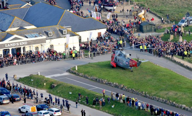 People lining the streets around a Royal Navy Sea King helicopter which carried the Olympic flame