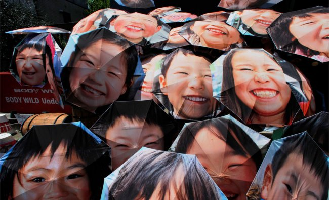 Japanese people hold umbrellas, with portraits of young survivors of the 2011 earthquake and tsunami