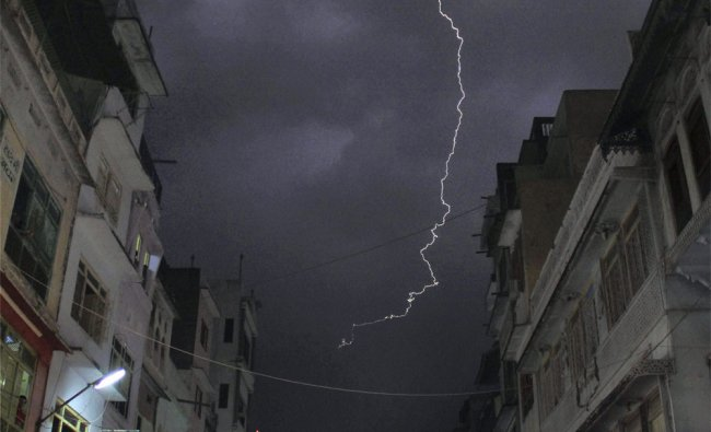 A flash of lightning is seen as devotees walk near the shrine of Khwaja Moinuddin Chishti
