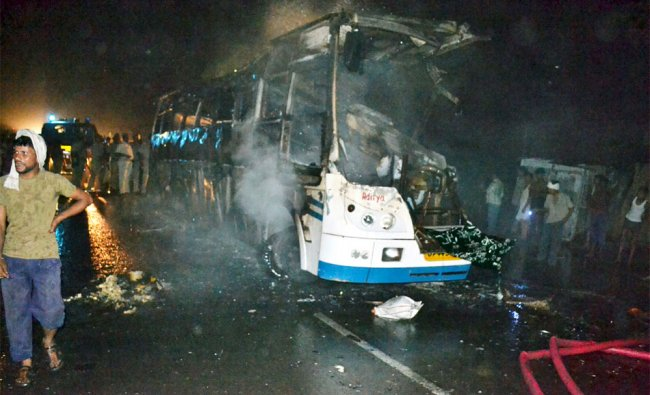 People stand near a charred bus that burst into flames late Friday night, in Bahraich, UP
