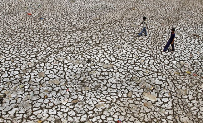 Boys walk on a parched portion of the River Sabarmati in Ahmadabad