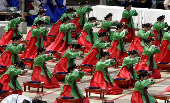 Girls wearing traditional dresses bow during the 40th Coming of Age Day ceremony