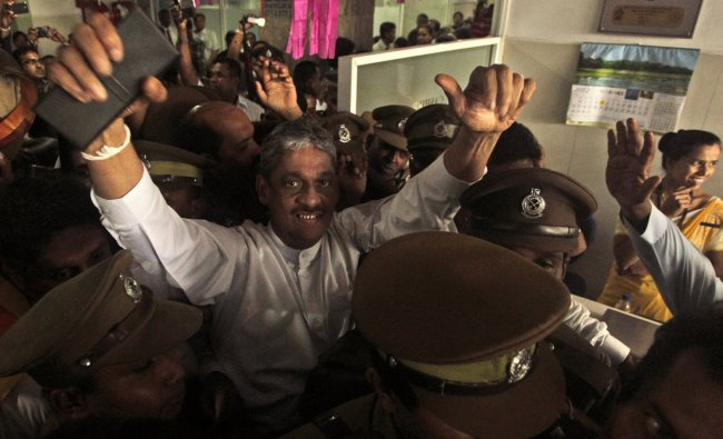 Sri Lankan former army chief Sarath Fonseka waves to his supporters as he is escorted out of a...