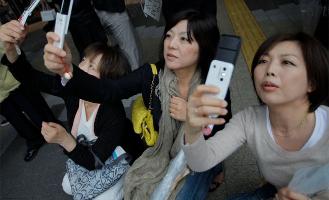 Visitors take photos of the Tokyo Skytree at its grand opening in Tokyo