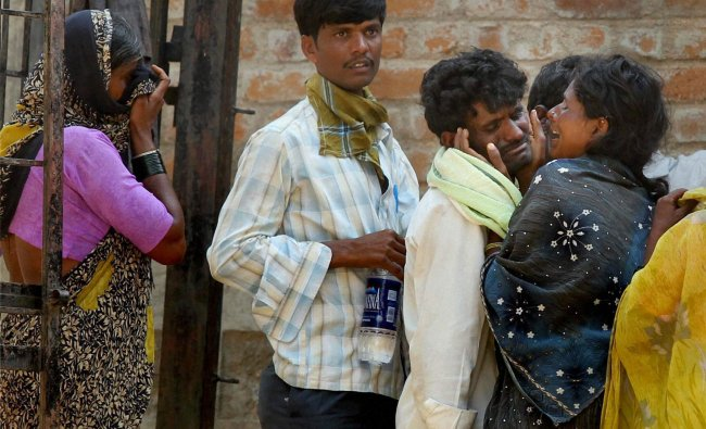 Relatives of the Hampi Express accident victims outside a mortuary in a hospital at Penukonda in...