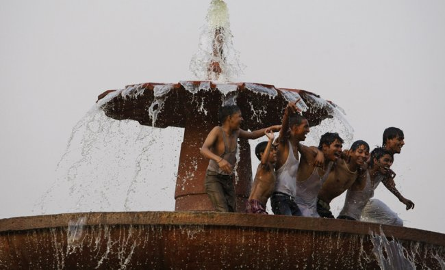 Youngsters enjoy cooling off in a fountain on a hot afternoon in New Delhi...