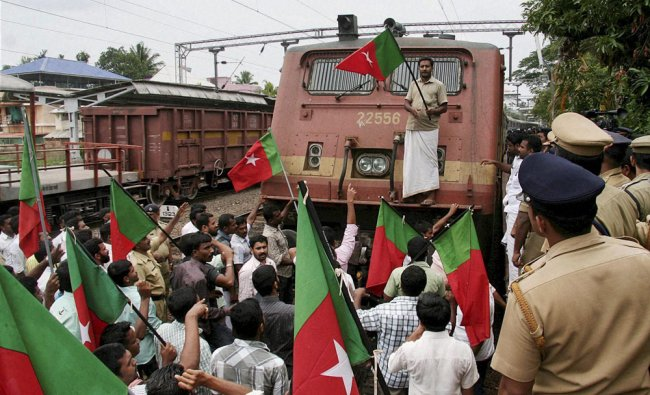Members of Social Democratic Party of India stop a train during a protest against petrol price hike