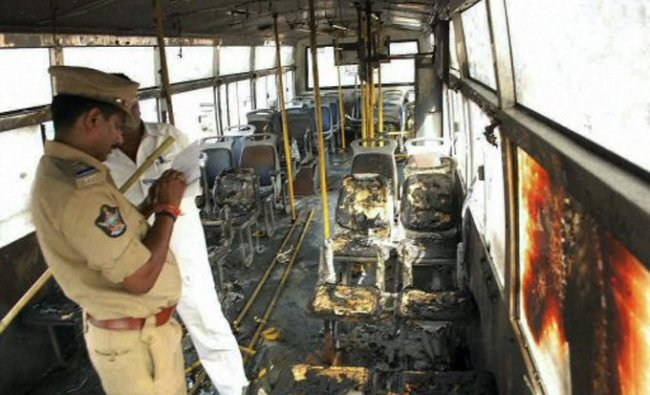 A policeman inspects a bus which was allegedly torched by the supporters of YS Jagan Mohan Reddy