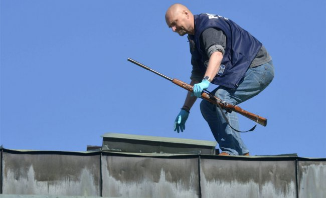A police officer retrieves the weapon of the gunman from the roof, in the center of Hyvinkaa