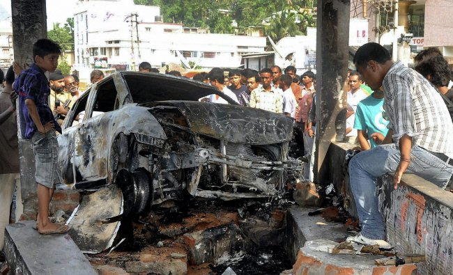 People looking at the charred vehicle which was torched by the irate mob