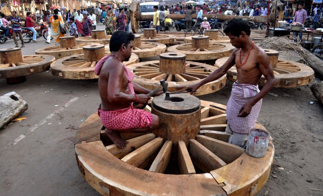 Carpenters completing the construction of the wheels for the chariots of Lord Jagannath, Lord...
