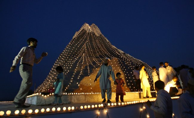 People gather in front of a decorated monument representing Chagai Mountain