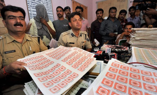 Police offcials showing fake stamp papers...