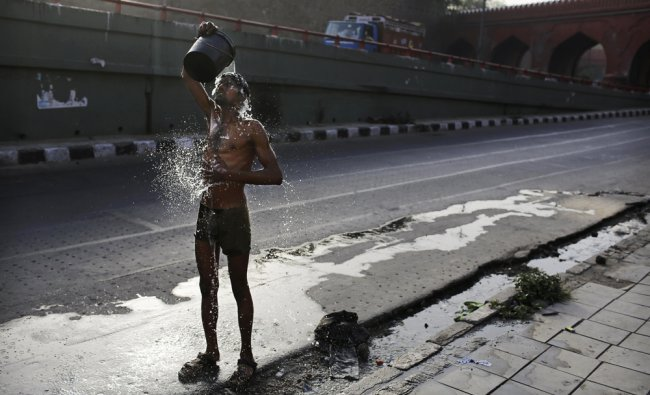 An Indian migrant laborer washes himself as he cools off on a warm morning ...