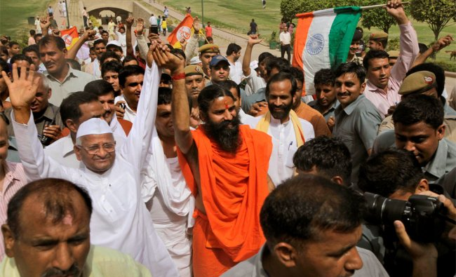 Anna Hazare and Ramdev greet supporters after paying their tributes at Rajghat
