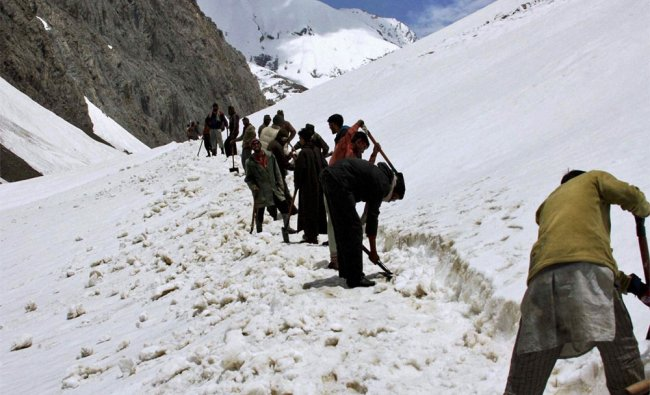 Labourers clear snow from the mountain tracks leading to the Amarnath cave shrine
