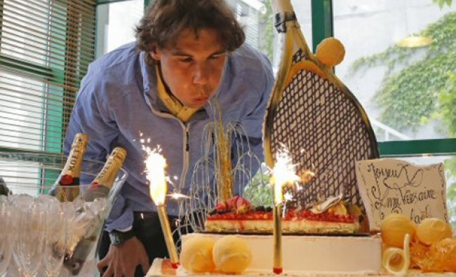 Rafael Nadal blows out candles on his birthday cake marking his 26th birthday