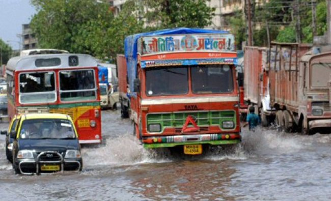 Vehicles move on a water logged road after a water pipeline burst in Mumbai on Sunday