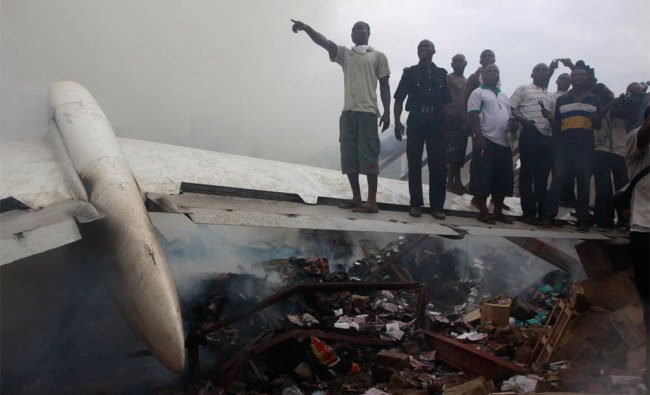 People gather at the site of a plane crash in Lagos, Nigeria