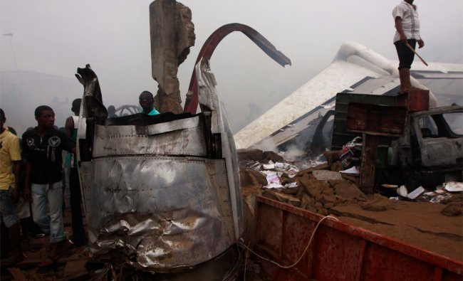 People stand on wreckage of a plane crash in Lagos, Nigeria,