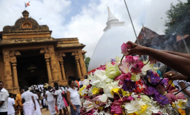 S Lankan Buddhists hold out flowers and pray during Poya festival at the Kelaniya Temple