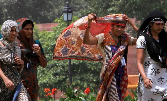 Young girls take protection against scorching heat on a hot day in New Delhi