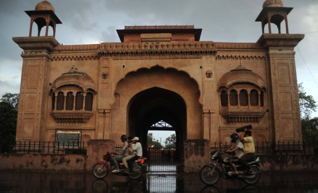Indian motorcyclists drive past a historical building during a downpour in Amritsar...