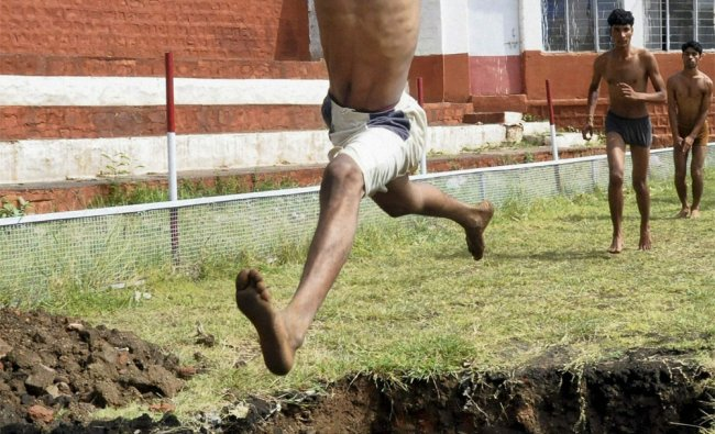 An aspirant attempts long jump during an Army recruitment rally