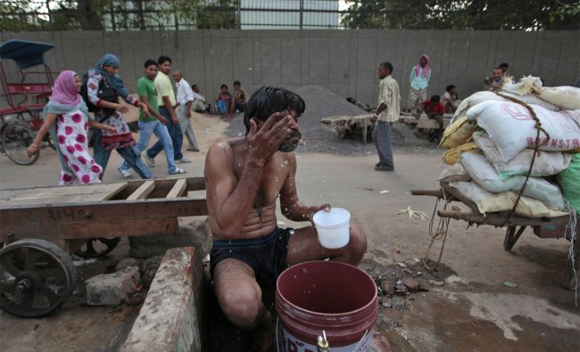 A daily wage laborer cleans himself after a hot day\'s work