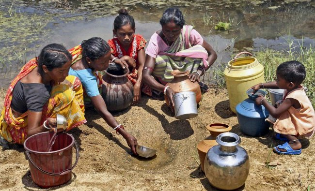 Villagers collecting water by digging the bed of Sal river
