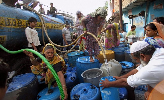 People collecting drinking water from a tanker at Okhla in New Delhi