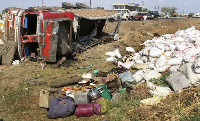 A truck, carrying workers and their families, overturned on a slippery road in western India...