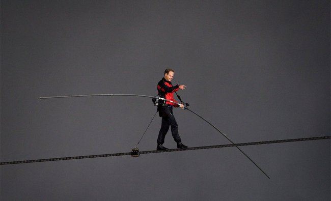 Nik Wallenda points to the crowd of onlookers as he nears completion of his tightrope walk