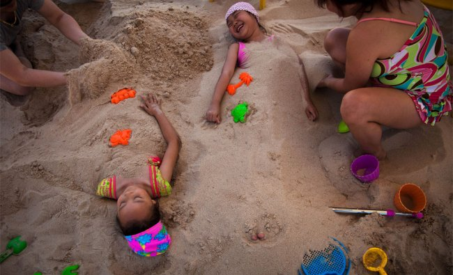 A Chinese couple cover sand on their children on the manmade beach at a park
