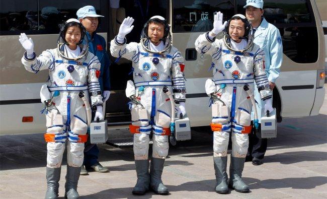 China\'s astronauts Liu Yang, Liu Wang, and Jing Haipeng wave before they depart for the launchpad
