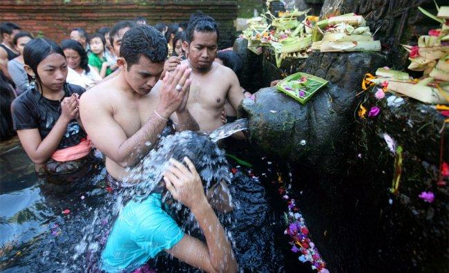 Balinese Hindus take a bath in holy water during Banyu Pinaruh in Bali, Indonesia