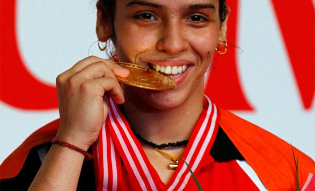 Saina Nehwal bites her medal after defeating China\'s Li Xuerui during their women\'s singles final