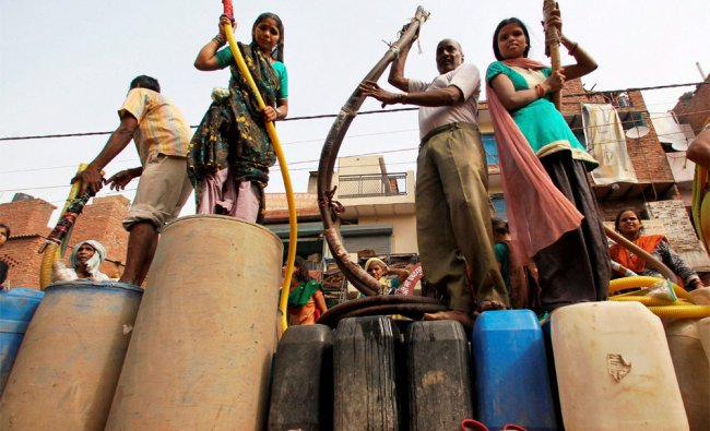 People waiting to collect drinking water from a tanker at Okhla industrial area in New Delhi