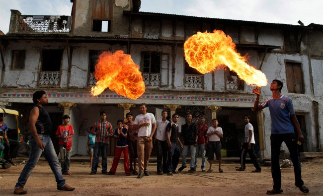 Indian youths practice fire stunts ahead of the annual Rath Yatra of Lord Jagannath in Ahmadabad