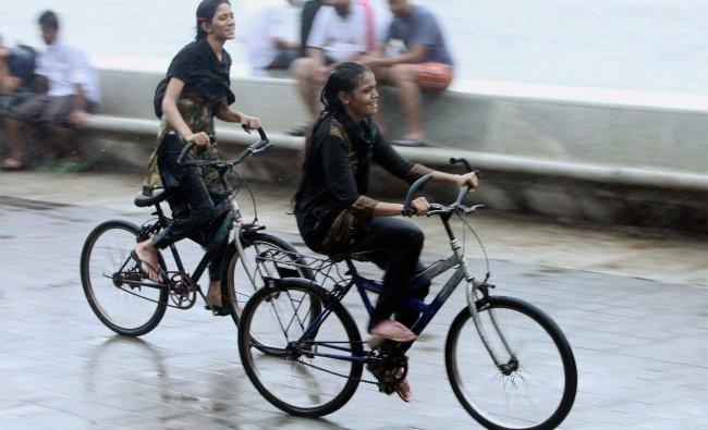Girls enjoy cycling during rains near Marine drive in Mumbai