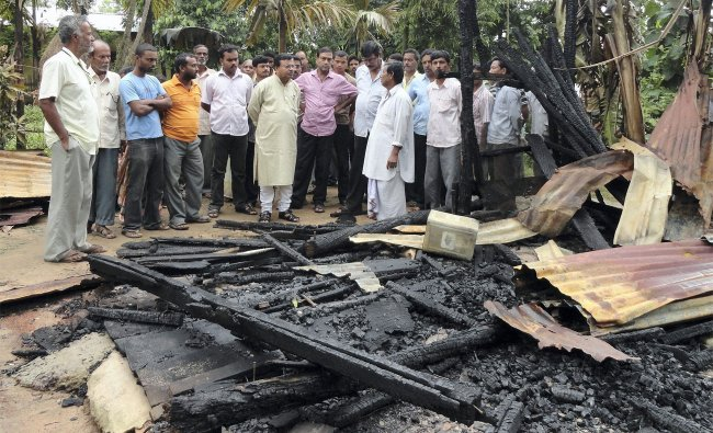 People look at the burnt house which is said to be doused by CPIM cadres