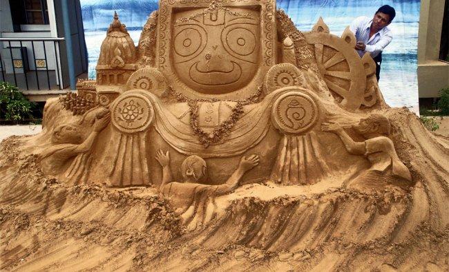Sand artist Subal Moharana creates a sand sculpture of Lord Jagannath and his chariot